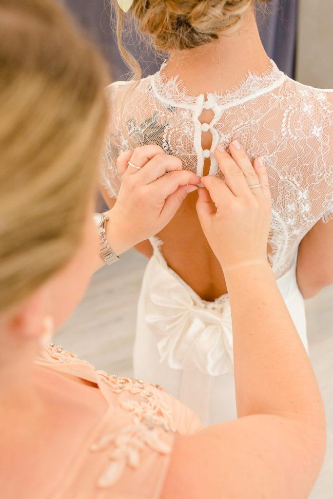 Brautjungfer hilft der Braut beim Brautkleid anziehen beim Getting Ready Shooting mit Fotograf Markus Winkelbauer